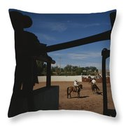 A Silhouetted Cowboy Watches Riders Throw Pillow by Raul Touzon