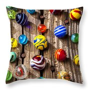 Marbles on wooden board Throw Pillow by Garry Gay