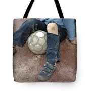 Boy with soccer ball sitting on dirty field Tote Bag by Matthias Hauser