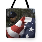Soldier Unfurls A New Flag For Posting Tote Bag by Stocktrek Images