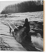 man on snowmobile crossing frozen fields in rural Forget canada Wood Print by Joe Fox