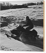 man on snowmobile crossing frozen fields in rural Forget Saskatchewan Wood Print by Joe Fox