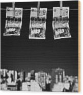 Three Twenty Pounds Sterling Banknotes Hanging On A Washing Line With Blue Sky Above A City Skyline Wood Print by Joe Fox