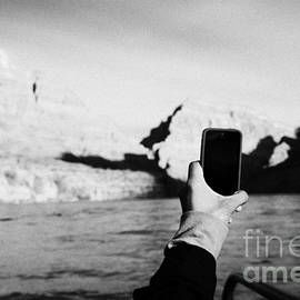 Joe Fox - man taking photos with smartphone during boat ride along the colorado river in the grand canyon Ariz
