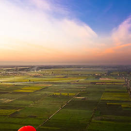 Mark E Tisdale - A Red Hot Air Balloon Landing in Egyptian Fields