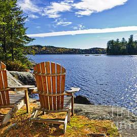 Adirondack chairs at lake shore by Elena Elisseeva