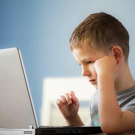 Boy Using Laptop by Samuel Ashfield