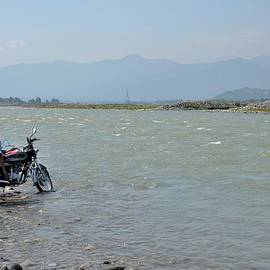 Imran Ahmed - Cleaning motorcycle at riverside Swat Valley Pakistan