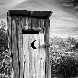 Desert Outhouse Under Stormy Skies by Lee Craig