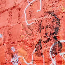 Etched man on a red brick wall by Jim Lepard
