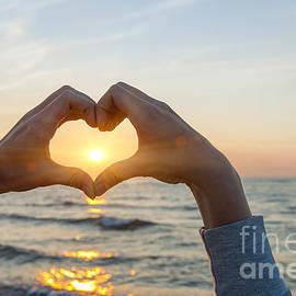 Fingers heart framing ocean sunset by Elena Elisseeva