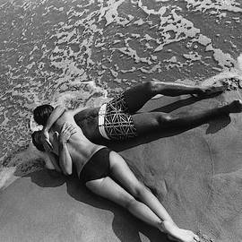 Models Embracing On A Beach by Mark Patiky