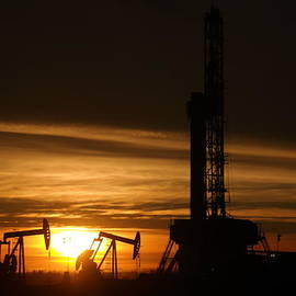Oil rig and two pumpjacks in the sunset by Jeff Swan