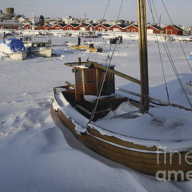 Ladi  Kirn - Old wooden boat under snow in frozen sea.