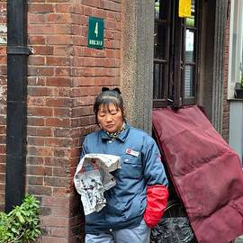Street cleaner reads paper Shanghai China by Imran Ahmed