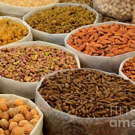 Variety of raw nuts for sale at outdoor street market Karachi Pakistan by Imran Ahmed