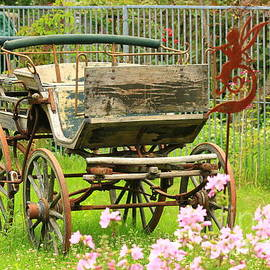 Vintage horse carriage in a flower bed  by Amanda Mohler