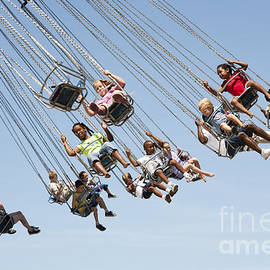 People On A Swing Carousel At A County Fair by William Kuta