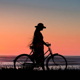 Silhouette Of Girl And Bike At Sunset Near The Sea. by Maggie Mccall
