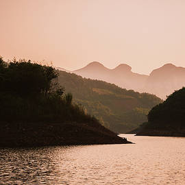 The Mountains And Lake Scenery In Sunset by Carl Ning