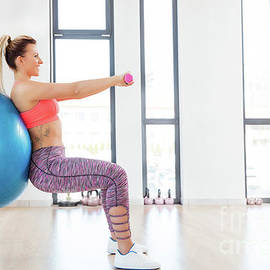 Michal Bednarek - Young woman training with fitball at fitness club.