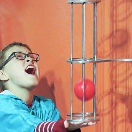 A Boy Tries to Catch a Ball at the Discovery Children's Museum,  by Derrick Neill