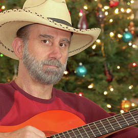A Cowboy with a Guitar by a Christmas Tree by Derrick Neill