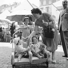 A family with infants at an open air market in Rome, 1955 - The Harrington Collection