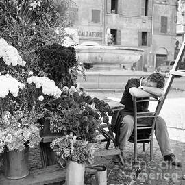 A flower vendor napping in a plaza in Rome, 1955 - The Harrington Collection