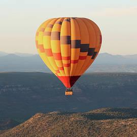 A Hot Air Balloon Soars Near Sedona, Arizona by Derrick Neill