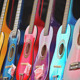 A Line of Shiny, Colorful, Miniature Guitars by Derrick Neill