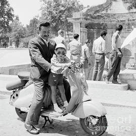 A man and his son on a 1955 Lambretta scooter, at a fountain in  - The Harrington Collection