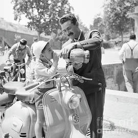 A man and his son on a 1955 Lambretta scooter, drinking water at - The Harrington Collection