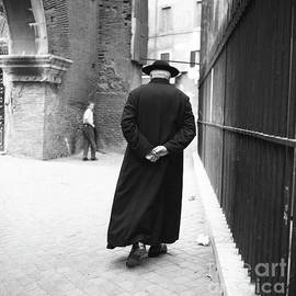 A priest walks down a street in Rome, 1955 - The Harrington Collection