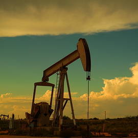 A pump jack and clouds Artesia New Mexico by Jeff Swan