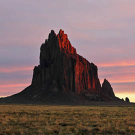 A Shiprock Landscape Against a Striated Sunrise Sky by Derrick Neill
