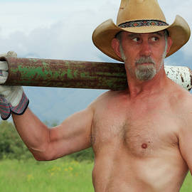 A Shirtless Cowboy Shoulders a Fence Post Driver by Derrick Neill