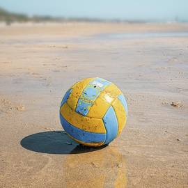 A volleyball on the beach by Carlos Caetano