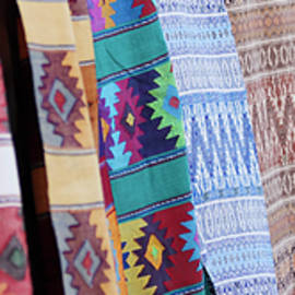 An Assortment of Colorful Blankets Hanging in a Row by Derrick Neill