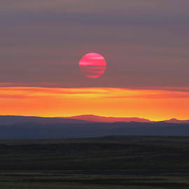 An Overcast Sky Filters the Rising Sun by Derrick Neill