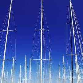 Geoff Childs - Artistic. Yacht Masts Reaching into a Vivid Blue Sky.