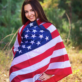 Oleksandr Masnyi - Beautiful model poses with the flag of the USA in the summer park