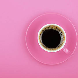 Black coffee in cup with saucer on pink by Anton Eine