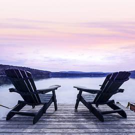 Chairs on lake dock by Elena Elisseeva