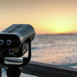 Coin-operated binoculars on pier at sunset overlooks ocean by Bradley Hebdon