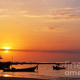 Fishing boat and sunset by Atiketta Sangasaeng