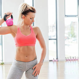 Michal Bednarek - Fit woman holding a kettlebell after finished workout.