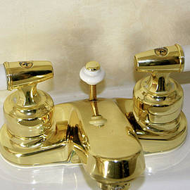 Gold And Porcelain Bathroom Faucet Installed On White Sink by Amelia Painter