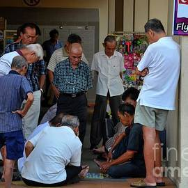 Group of Chinese men watch a game of checkers in Singapore neighborhood