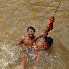 Hanging on Cambodia boy in River Siem Reap  by Chuck Kuhn